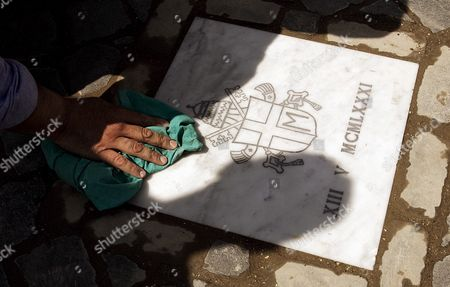 Vatican Workers Place a Marble Slab on the Exact Spot in St Peter's Square where Pope John Paul Ii was Shot in an Assassination Attempt 25 Years Ago Friday 12 May 2006 the Slab Which is Engraved with the Late Pope's Coat of Arms Replaced a Red-painted Cobblestone Which Had Indicated the Location where Pope Wojtyla was Hit by Bullets Fired by Turkish Terrorist Ali Agca on 13 May 1981 the Pope was Greeting and Blessing a Cheering Crowd From His 'Popemobile' After a General Audience when He was Shot the 25th Anniversary of the Assassination Attempt Will Be Celebrated Here on Saturday with a Number of Events Expected to Draw Some 20 000 People Our Lady of Fatima Statue From Portugal the Statue Will Be Lifted by Helicopter From the Banks of the Tiber River in Front of Castel Sant'angelo and Brought to the Head of Via Della Conciliazione Vatican City State (holy See) Vatican City