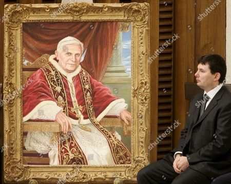 An Unidentified Man Looks a Framed Portrait of Pope Benedict Xvi in a Paolo Vi's Hall at the Vatican 12 December 2007 the Portrait Made by Russian Painter Natalia Tsarkova was Given to the Pope at the End of the Weekly Wednesday General Laudience in the Painting the Pope is Seen Seated on the Throne of Pope Leone Xiii Vatican City State (holy See) Vatican City