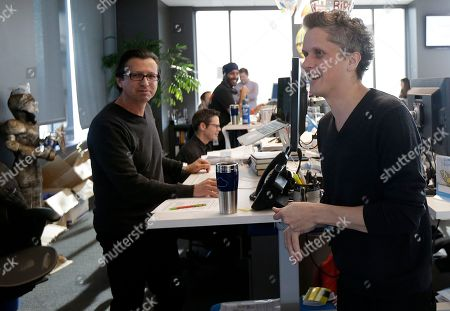 Box CEO and co-founder Aaron Levie, right, smiles while talking with employees as he is interviewed at his office in Redwood City, Calif., . The heads of Apple, Ford and Goldman Sachs said that they don't support the executive order that President Donald Trump signed last week, which bans immigrants from seven Muslim-majority countries from entering the U.S. Google said it is donating cash to organizations that support immigrants. Other companies said they will help employees affected by the ban or, in the case of Starbucks, hire refugees