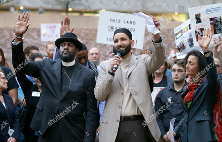 Stock Image of Iman Omar Suleiman, Rabbi Nancy Kasten, right, Michael W. Waters Iman Omar Suleiman, center, raises his hand with Rabbi Nancy Kasten, right, and the Rev. Michael W. Waters while speaking before a candlelight vigil at Thanksgiving Square in downtown Dallas, . Community activist gathered to protest against President Donald Trump's executive order temporarily banning immigrants from seven Muslim-majority countries from entering the U.S. and suspending the nation's refugee program
