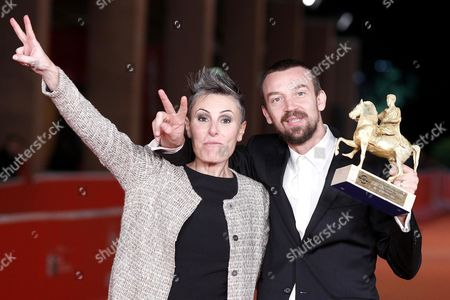 Stock Photo of Alberto Fasulo Holds the 'Golden Marc'aurelio' Award He Received For 'Tir' with His Wife Nadia Trevisan at the 8th Annual Rome Film Festival in Rome Italy 16 November 2013 Italy Rome