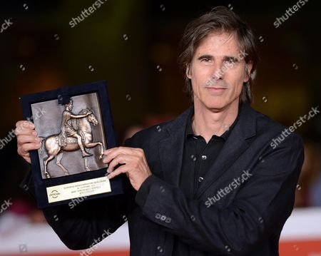 Stock Photo of Brazilian Director Walter Salles Holds His Marc'aurelio Acting Award As He Arrives For the Premiere of the Movie 'Soul Boys of the Western World Spandau Ballet the Film' at the 9th Annual Rome Film Festival in Rome Italy 20 October 2014 the Festival Runs From 16 to 25 October Italy Rome
