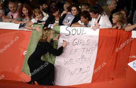 Stock Picture of British Director and Producer George Hencken Signs an Autograph on an Italian Flag From Fans Reading 'Soul Girls of the Western World' As She Arrives For the Premiere of the Movie 'Soul Boys of the Western World Spandau Ballet the Film' at the 9th Annual Rome Film Festival in Rome Italy 20 October 2014 the Festival Runs From 16 to 25 October Italy Rome