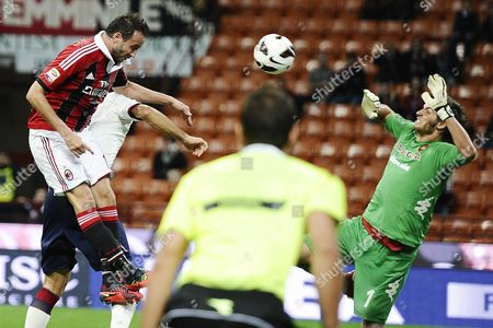 A C Milan Forward Gianpaolo Pazzini (l) Heads the Ball Past Cagliari Goalkeeper Michael Agazzi During Thier Serie a Soccer Match at the Giuseppe Meazza Stadium in Milan Italy 26 September 2012 Italy Milan