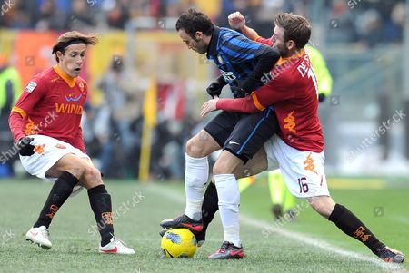 Italian Forward of Inter Milan Giampaolo Pazzini (c) Vies For the Ball with Brazilian Midfielder of As Roma Rodrigo Taddei (l) and His Teammate Daniele De Rossi (r) During the Serie a Soccer Match Between As Roma and Inter Milan at the Olimpico Stadium in Rome Italy 05 February 2012 Italy Rome
