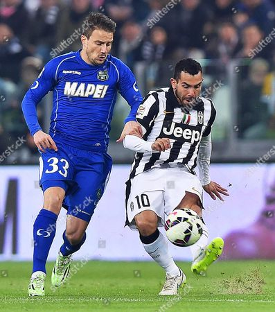 Juventus' Carlos Tevez (r) in Action Against Sassuolo's Matteo Brighi (l) During the Italian Serie a Soccer Match Between Juventus Fc and Us Sassuolo Calcio at the Juventus Stadium in Turin Italy 09 March 2015 Italy Turin