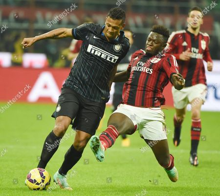 Inter Milan's Colombian Midfielder Fredy Guarin (l) Vies For the Ball with Ac Milan Ghanaian Midfielder Sulley Ali Muntari During the Italian Serie a Soccer Match Between Ac Milan and Fc Inter at Giuseppe Meazza Stadium in Milan Italy 23 November 2014 Italy Milan