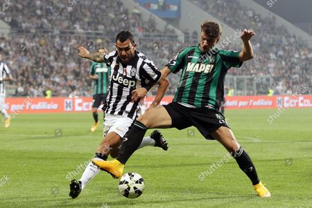Luca Antei of Us Sassuolo (r) Fights For the Ball with Carlos Tevez of Fc Juventus During the Italian Serie a Soccer Match Between Sassuolo and Juventus at the Mapei Stadium in Reggio Emilia 18 October 2014 Italy Rome