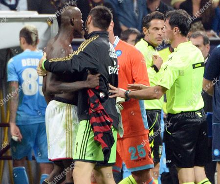 Ac Milan Forward Mario Balotelli (l) is Held by Teammate Goalkeeprer Marco Amelia at the End of the Serie a Soccer Match Beween Ac Milan and Napoli at the Giuseppe Meazza Stadium in Milan Italy 22 September 2013 Italy Milan