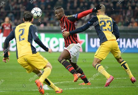 Ac Milan Forward Mario Balotelli (c) Vies For the Ball with Atletico Madrid's Brazilian Defender Joao Miranda De Souza (r) During the Uefa Champions League Round of 16 First Leg Soccer Match Between Ac Milan and Atletico Madrid at the Giuseppe Meazza Stadium in Milan Italy 19 February 2014 Italy Milan