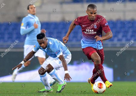 Ss Lazio's Ogenyi Onazi (l) in Action Against Trabzonspor's Florent Malouda (r) During the Uefa Europa League Group J Soccer Match Between Ss Lazio and Trabzonspor at the Olimpico Stadium in Rome Italy 12 December 2013 Italy Rome