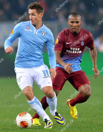 Ss Lazio's Miroslav Klose (l) in Action Against Trabzonspor's Florent Malouda (r) During the Uefa Europa League Group J Soccer Match Between Ss Lazio and Trabzonspor at the Olimpico Stadium in Rome Italy 12 December 2013 Italy Rome