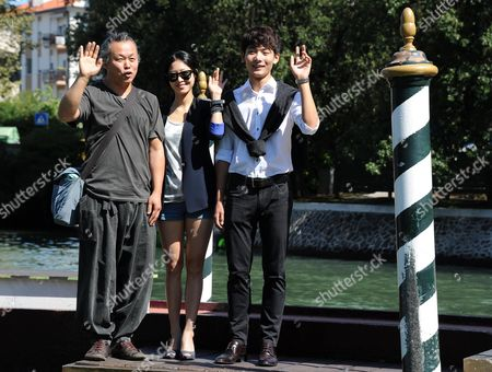 Stock Picture of South Korean Film Director Kim Ki-duk (l) Waves Next to Compatriots Actress Lee Eun-woo (c) and Actor Seo Young-joo (r) Upon Their Arrival at the Lido of Venice to Promote His Movie 'Moebius' Presented out of Competition at the 70th Annual Venice International Film Festival in Venice Italy 02 September 2013 the Festival Runs From 28 August to 07 September Italy Venice