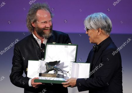 German Director Philip Groning (l) Receives From Member of the Venezia 70 Jury Japanese Musician Composer and Actor Ryuichi Sakamoto (r) the Special Jury Award For the Movie 'Die Frau Des Polizisten (the Police Officer's Wife)' During the Closing Award Ceremony of the 70th Venice International Film Festival in Venice Italy 07 September 2013 Italy Venice