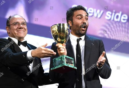 Stock Picture of Italian Director Saverio Costanzo (r) Accepts the Volpi Cup Award For Best Actor on Behalf of Us Actor Adam Driver (not Pictured) For His Role in the Movie 'Hungry Hearts' From Italian Director and Venezia 71 Jury Member Carlo Verdone (l) During the Awarding Ceremony of the 71st Annual Venice International Film Festival in Venice Italy 06 September 2014 the Festival Runs From 27 August to 06 September Italy Venice