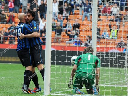 Argentinian Forward of Inter Diego Milito (c) Jubilates with His Teammate Argentinian Midfielder Esteban Cambiasso After Scoring a Goal During the Italian Serie a Soccer Match Fc Internazionale Milano Vs Cfc Genoa at Giuseppe Meazza Stadium in Milan Italy on 01 April 2012 on the Right French Goalkepeer of Genoa Sebastien Frey Italy Milano