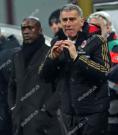 Dutch Coach of Ac Milan Clarence Seedorf (l) Looks on As Assistant Coach Mauro Tassotti (r) Gives Directions to His Players From the Sideline During the Italian Serie a Soccer Match Between Ac Milan and Hellas Verona at Giuseppe Meazza Stadium in Milan Italy 19 January 2014 Italy Milan