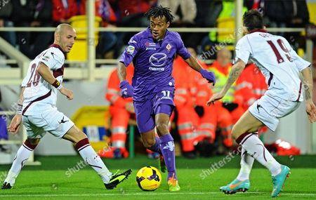 Acf Fiorentina's Colombian Midfielder Juan Guillermo Cuadrado (c) Fights For the Ball with Pasquale Schiattarella (l) and Leandro Greco (r) of Livorno Calcio During the Italian Serie a Soccer Match Between Acf Fiorentina and As Livorno at Artemio Franchi Stadium in Florence Italy 05 January 2014 Italy Florence