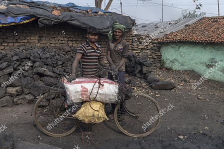 Villagers with a bicycle loaded with bags of scavenged coal ready to be sold on a nearby market, Panday Bera, a village near Jharia coal field
