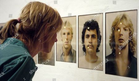 A Young Woman Looks at an Artwork by Sophie Calle Entitled 'Targets' Consisting of a Collection of Photos of Young Criminals Which Were Used by Us Policemen For Their Shooting Training at the Sophie Calle Retrospective in Berlin on Friday 10 September 2004 Calle was Born in 1953 in Paris and Ranks Among the Most Prominent French Artists Germany Berlin