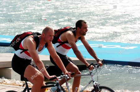 German Men' S Quadruple Sculls Team-members Marco Geisler and Andre Wilms (l) Bike Along the Schinias Olympic Rowing Center Because They Could not Practice on the Water Due to Strong Winds Sunday 15 August 2004 Epa/dpa Achim Scheidemann Greece Schinias