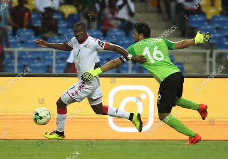 Prejuce Nakoulma of Burkina Faso evades tackle from goalkeeper Aymen Mathlouthi of Tunisia on his way to score