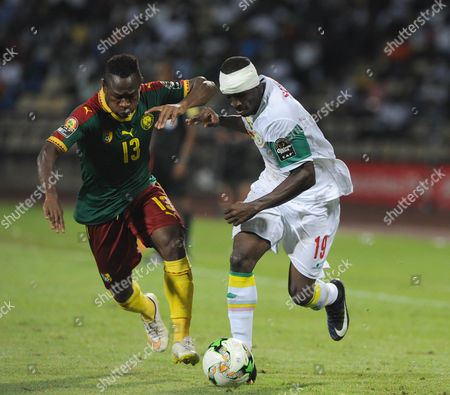 Christian Bassogog of Cameroon (L) challenges Saliou Ciss of Senegal (R),