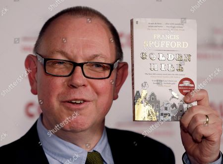 Author Francis Spufford holds a copy of his book 'Golden Hill' as he poses for the media at the Costa Book Awards 2016 in London