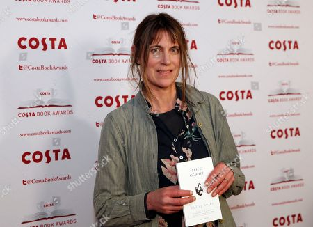 Author Alice Oswald holds up her book 'Falling Awake', winner of the poetry category, as she poses for the media at the Costa Book Awards 2016 in London