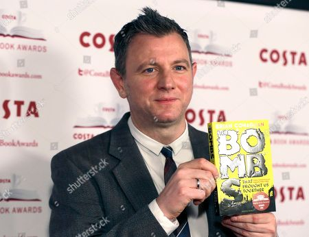 Author Brian Conaghan holds up his book 'The Bombs that Brought us Together' winner of the children's category, as he poses for the media at the Costa Book Awards 2016 in London
