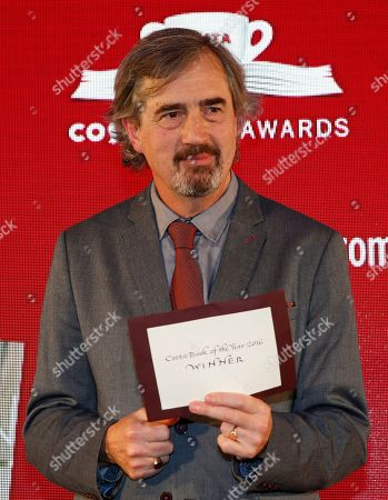 """Winner of the Costa Book Award 2016 Sebastian Barry poses onstage after winning the award for his book 'Days without End"""" in London"""