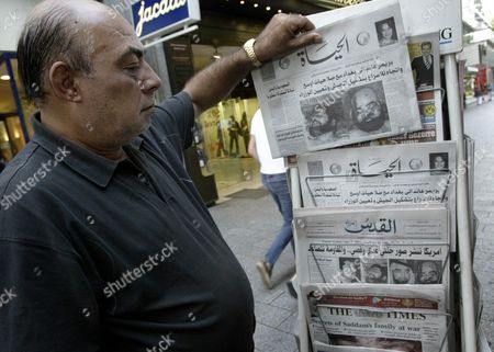 Palestinian Fathi Afana Buys an Arab Newspaper at a Newstand in Duesseldorf Friday 25th July 2003 All the Titles on Display Showed Front Page Images of Uday and Qusay Hussein Sons of Saddam who Died Earlier in the Week in a Firefight with Us Troops Pictures of the Two Men Were Released by Us Authorities Yesterday Epa Photo/dpa/daniel Loeb Germany Duesseldorf