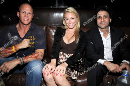 Stock Picture of Brenden Theaters owner Johnny Brenden and Playboy Playmate Miss October 2008 Kelly Carrington and Palms Resort owner George Maloof at the Playboy Club in Las Vegas