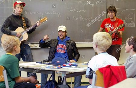 Swiss Pop Singer Patrick Nuo (c) and Guitarists Ian O'brian-docker (l) and Stefan Knoess (r) Play the Song 'Reanimate' Requested by the Pupils in Front of Class 4c of the Ikarus Elementary School in Berlin-mariendorf Germany Thursday 13 May 2004 the Surprise Performance was Possible Because Nuo is in Berlin For One Day For the Start of the 1st Pokemon-colloseum-championships Germany Berlin