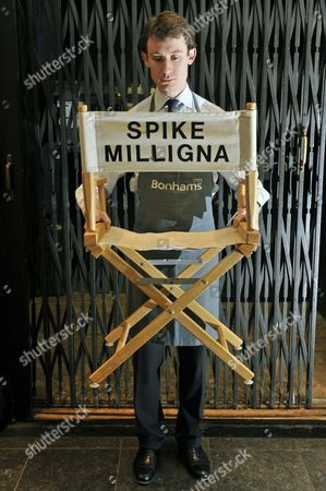 """A Bonhams assistant holds a director's chair featuring the words """"Spike Milligna"""" on the back with an estimate of £250-300."""
