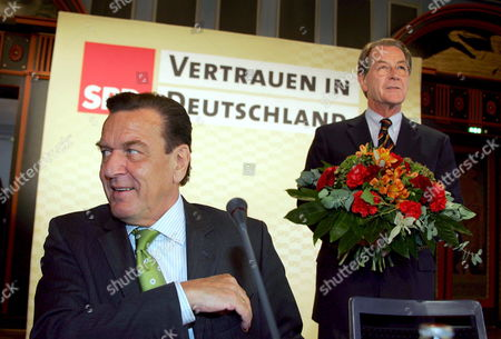 German Chancellor Gerhard Schroeder (l) Sits in the Town Hall of Kassel While Chairman of the Social Demorats (spd) Franz Muentefering (r) Holds a Bouquet of Flowers in Kassel Germany Friday 05 August 2005 the Chairmanship of the Social Democrats (spd) Met in Kassel to Settle the Last Details For the Federal Election Campaign After the Meeting More Than 300 Delegates of All Constituencies Will Debate Over Strategy Issues Germany Kassel