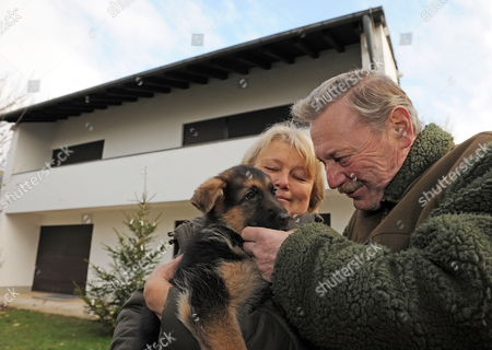 Stock Photo of Rupert and Therese Hofbauer Hold Shepherd Dog Puppy Lea in Front of the Private House of Pope Benedict Xvi in Pentling Germany 15 December 2009 the Two-month-old Dog Will Guard the House in the Future the Hofbauers Take Care of Pope Benedict's House Germany Pentling
