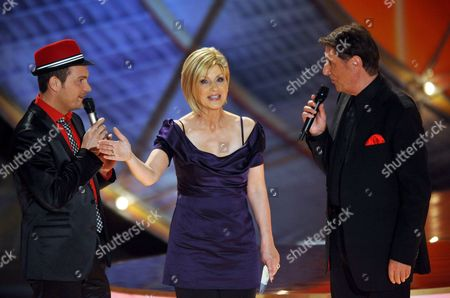 German Musician Roger Cicero (l) and Austrian Singer and Composer Udo Juergens (r) Talk with Host Carmen Nebel (c) During the Live Broadcast German Zdf Television Show 'Willkommen Bei Carmen Nebel' in Erfurt Germany on 09 May 2009 Germany Erfurt