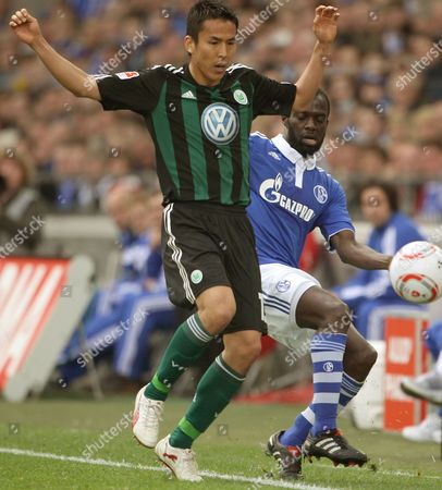Schalke's Hans Sarpei (r) Vies For the Ball with Wolfsburg's Makoto Hasebe (l) During Their German Bundesliga Match on 09 April 2011 in Gelsenkirchen Germany (attention: Embargo Conditions! the Dfl Permits the Further Utilisation of the Pictures in Iptv Mobile Services and Other New Technologies Only No Earlier Than Two Hours After the End of the Match the Publication and Further Utilisation in the Internet During the Match is Restricted to Six Pictures Per Match Only ) Germany Gelsenkirchen