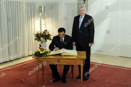 Stock Image of The Bavarian Prime Minister Horst Seehofer (r) Looks on As Chinese Vice Prime Minister Li Keqiang (l) Signs the Guest Book of the Bavarian State Chancellery in Munich Germany 08 January 2011 Reports State That Vice Premier Li Kequiang is on a Visit to Europe Which Includes Spain Germany and Britain Germany Munich