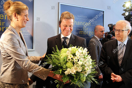 As German Economy Minister Rainer Bruederle (r) Looks on Free Democratic Member of the European Parliament Silvana Koch-mehrin (l) Presents a Bouquet of Flowers to German Foreign Minister and Still-actingáchairman of the Free Democratic Party (fdp) Guido Westerwelle (c) at a Party Executives Meeting in Berlin on 04 April 2011 Westerwelle who Announced 03 April He was Resigning As Leader of the Fdp Could Also Renounce His Role As Deputy Chancellor Fdp General Secretary Christian Lindner 32 (unseen) Has Been Considered As Possible Successor to Westerwelle the Previous Day Westerwelle Had Announced That He Would not Seek Re-election As Fdpáchairman at the Upcoming Party Convention in May Germany Berlin