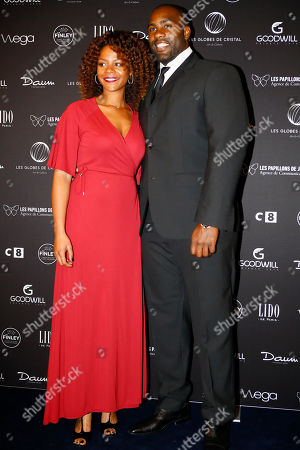 French heavyweight judoka and Rio 2016 Olympic ChampionTeddy Riner, right, and his wife Luthna Plocus pose during a photo call at the Lido cabaret on the Champs Elysees, to take part in the Crystal Globes awards ceremony in Paris