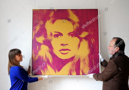 Staff Members of the Gallery Florian Sundheimer Hold a Portrait of Brigitte Bardot by Andy Warhol During the Presentation of Gunter Sachs Auction Items in Munich Germany 23 April 2012 the Piece is One of 300 Items of the Gunter Sachs Collection to Be Auctioned at Sotheby's in London Britain on 22 and 23 May Germany Munich