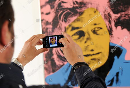 A Visitor of the Gallery Florian Sundheimer Photographs a Gunter Sachs Portrait by Andy Warhol with a Cell Phone During the Presentation of Gunter Sachs Auction Items in Munich Germany 23 April 2012 the Piece is One of 300 Items of the Gunter Sachs Collection to Be Auctioned at Sotheby's in London Britain on 22 and 23 May Germany Munich
