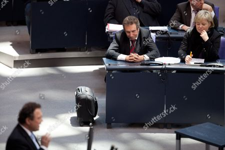 Joint Party Leaders of 'The Left' Party Klaus Ernst (c) and Gesine Loetzsch (r) Watch German Minister of Interior Hans-peter Friedrich (l in Foreground) Commenting on a Debate Concerning the Controversial Surveillance of 'The Left' Party Deputies to the German 'Bundestag' Parliament by Intelligence Services at the German Parliament in Berlin Germany 26 January 2012 Germany Berlin