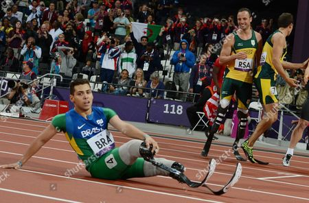 Stock Image of Oscar Pistorius (2-r) and Team Mate Arnu Fourie (r) of South Africa Look at Defeated Alan Fonteles Cardoso Oliveira of Brazil (l) After They Along with Samkelo Radebe and Zivan Smit (both Unseen) Won the Gold Medal in the Men's 4x100m Relay -t42-46 Final at Olympic Stadium During the London 2012 Paralympic Games London Britain 05 September 2012 United Kingdom London