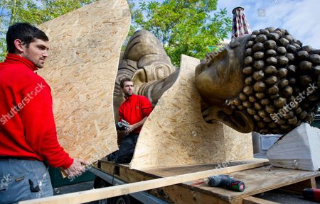 Workers Remove a Lying Buddha Figure at Viktualienmarkt Square in Munich Germany 23 September 2013 the Controversial Artwork by Han Chong with the Title 'Made in Dresden' Caused a Stir During the Time of Its Exhibition Germany Munich