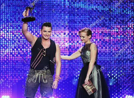 Austrian Musician Andreas Gabalier (l) on Stage with the Bambi Trophy in the Category 'Shooting Stars' Next to Presenter Mirjam Weichselbraun During the Award Ceremony in Duesseldorf Germany 22 November 2012 the Bambis Are the Main German Media Awards and Are Presented For the 64th Time Germany Duesseldorf