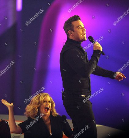 British Entertainment Robbie William Former Member of Hit Vocal Group Take That Performing in the Popular Sunday Night Programme 'Wetten Dass ? (you Bet??) at Bremen Tv Studios Late 3 November 2012 Robbie and His Wife Ayda Field Recently Celebrated the Birthday of a Baby Girl Theodora Rose Behind Him German Actress Barbara Schoenberger Prepares a Playful Slap on His Backside Germany Bremen