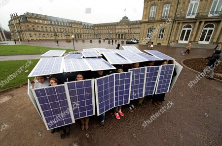 Stock Image of Pupils Carry Solar Panels As Part of the Performance in a Public Space 'Testudo Solaris' on Schlossplatz Square in Stuttgart ágermany 07ádecember 2013 the Performance Electrics Gmbh was Directed by Artist Pablo Wendel an Employes Solar Panel Shields in a Roman Military Formation Germany Stuttgart